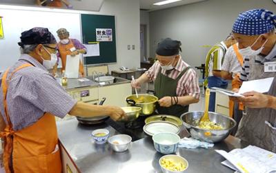 キッチンで料理をしている人達  中程度の精度で自動的に生成された説明